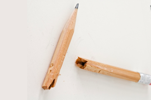 A pencil broken in two from the middle on a white background