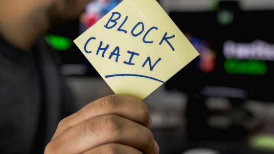 a hand holding a stick note with the word blockchain on it