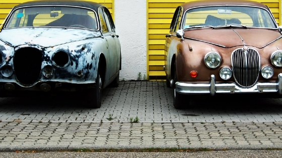 one grey vintage car on left and one brown vintage car on right