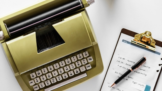 Gold typewriter on left and a sheet of paper on a pad with pen on right