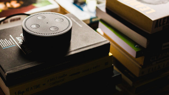 Amazon echo dot, a conversational UI based device, kept on a pile of books