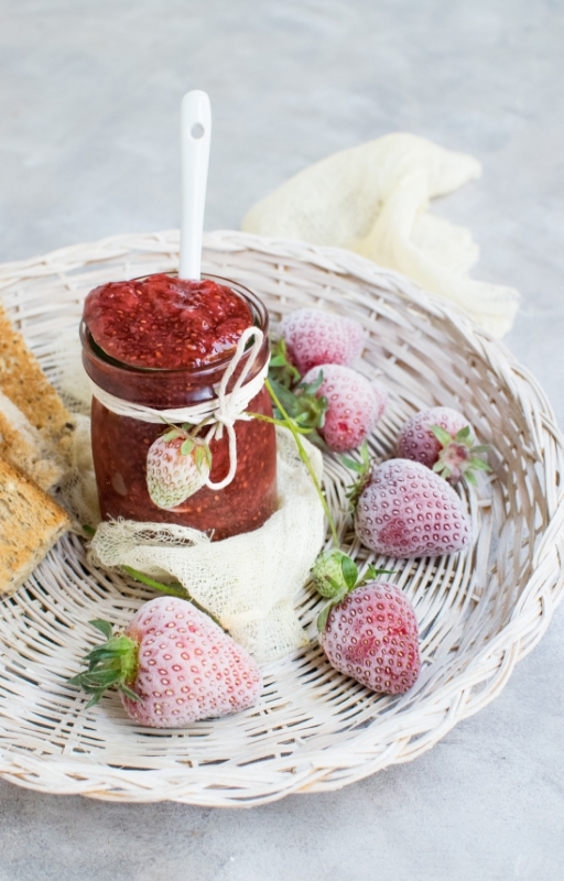 basket of strawberry fruits with jar of jam