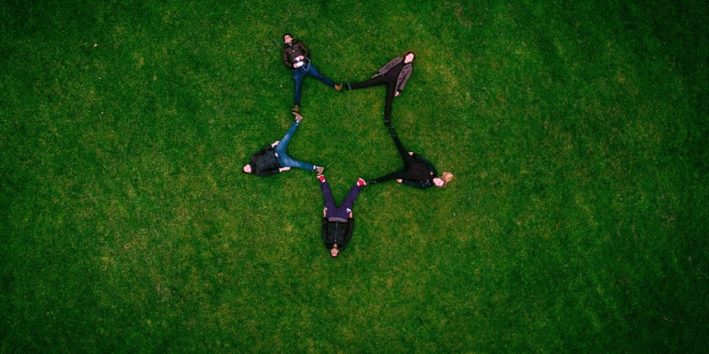 Image with five people resting on the ground with grass. There feet are joined to each other in form of a star.