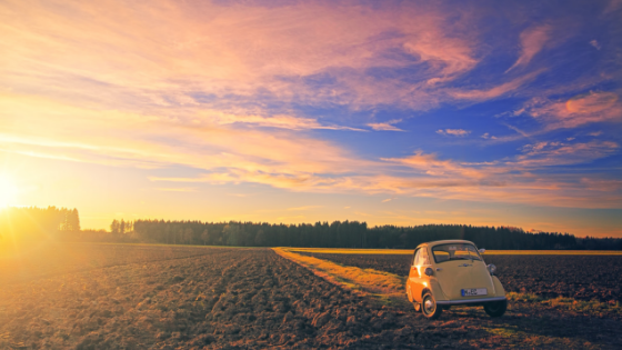 a car parked in an open field with sun setting in the distance