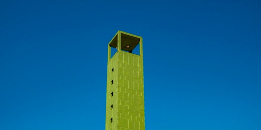 Image of a tall green building with a blur background