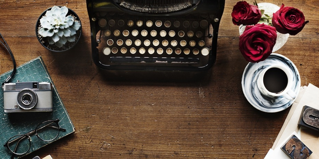 Image of a typewriter placed at the center of a wooden background where there is a tea pot and a flower vase on the left side and a camera on right side