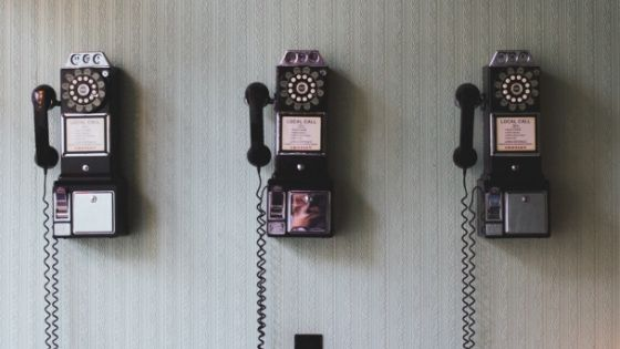 three traditional phones on the wall