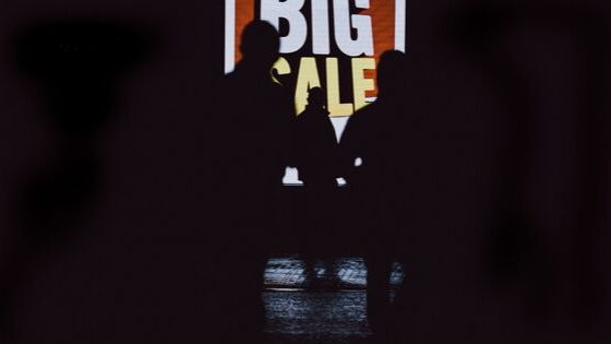 a man standing near the board that reads 'big sale'