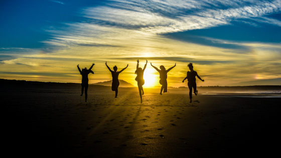 a group of people jumping in the air with sun rising in the background