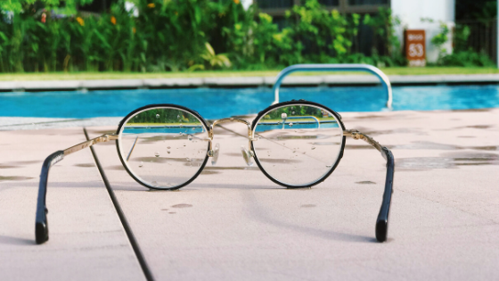 a pair of spectacles placed near a swimming pool