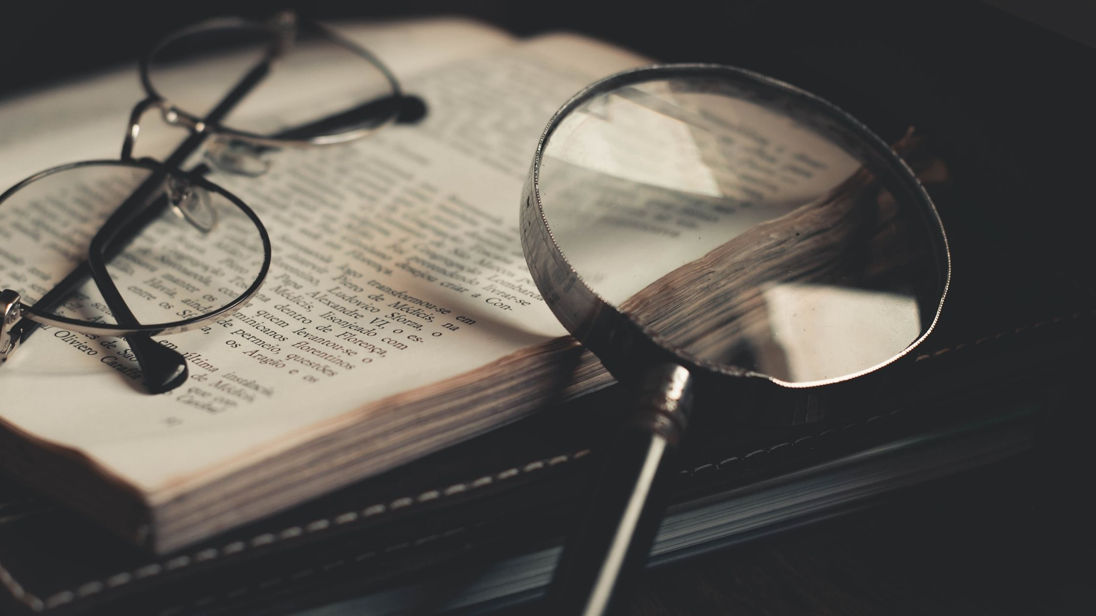 An open book, a pair of glasses and a magnifying glass can be seen kept together.