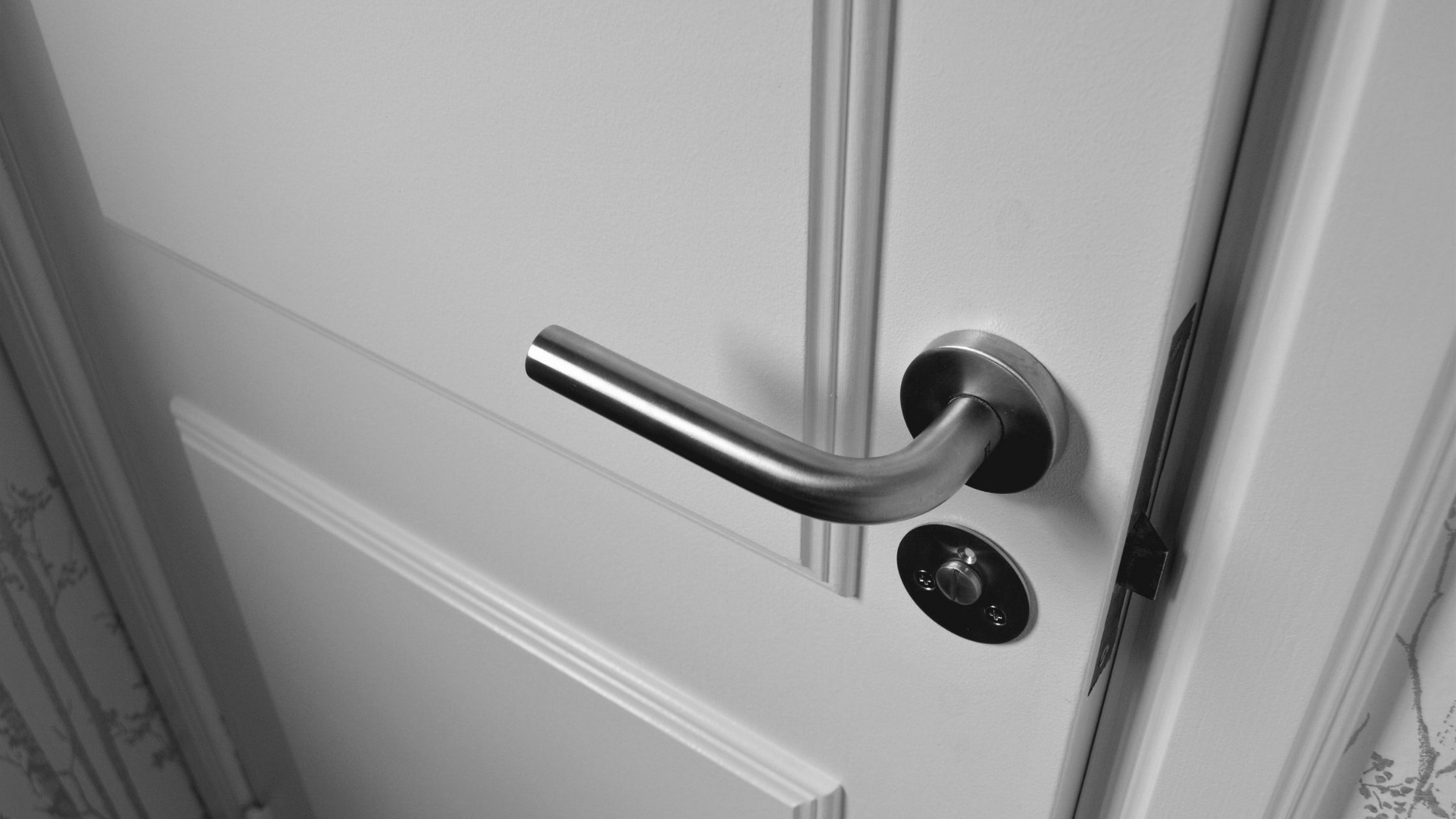 The door handle on a white door can be seen.