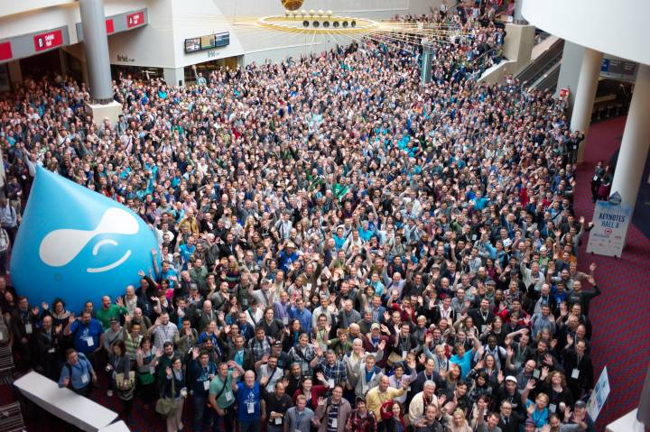 An image of a crowd in an auditorium where the left side is having a big balloon of Drupal logo