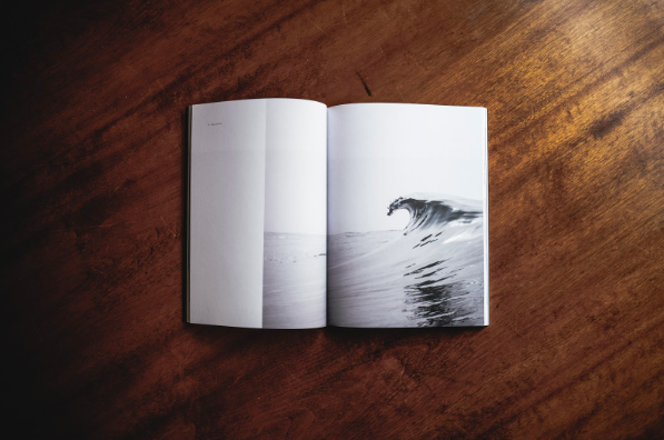 An open book, showing an image of ocean tides, kept on the table