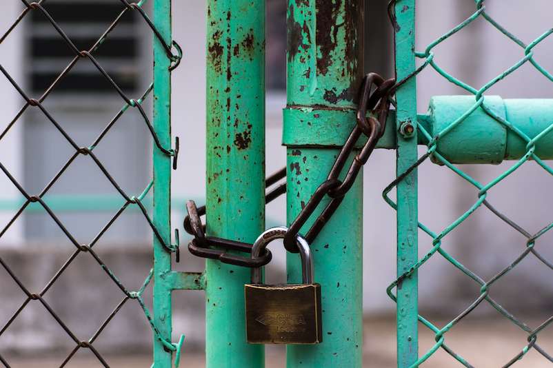 A house lock put up on a green coloured structure