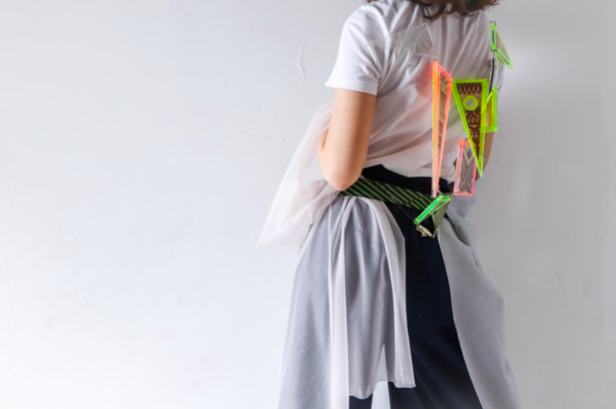 Illustration image, representing design thinking, showing a back-facing girl in white, blue and green color clothes with a series of triangle shapes designs attached in a wire enclosed around her neck