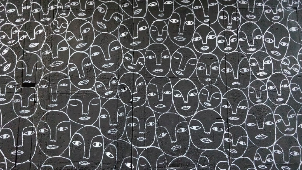 Illustartaion image showing repetitive human faces with eyes, nose, and lips were drawn in white colour on a grey background wall