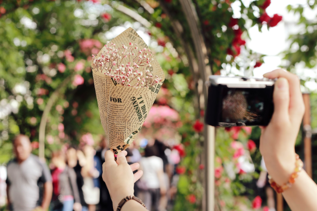 Image, representing microservices, showing hands of a person clicking the picture of a handmade bouquet in one and camera on the other and blurred flowers, trees, people in the background