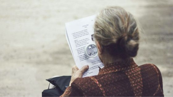 woman reading with magnifying glasses