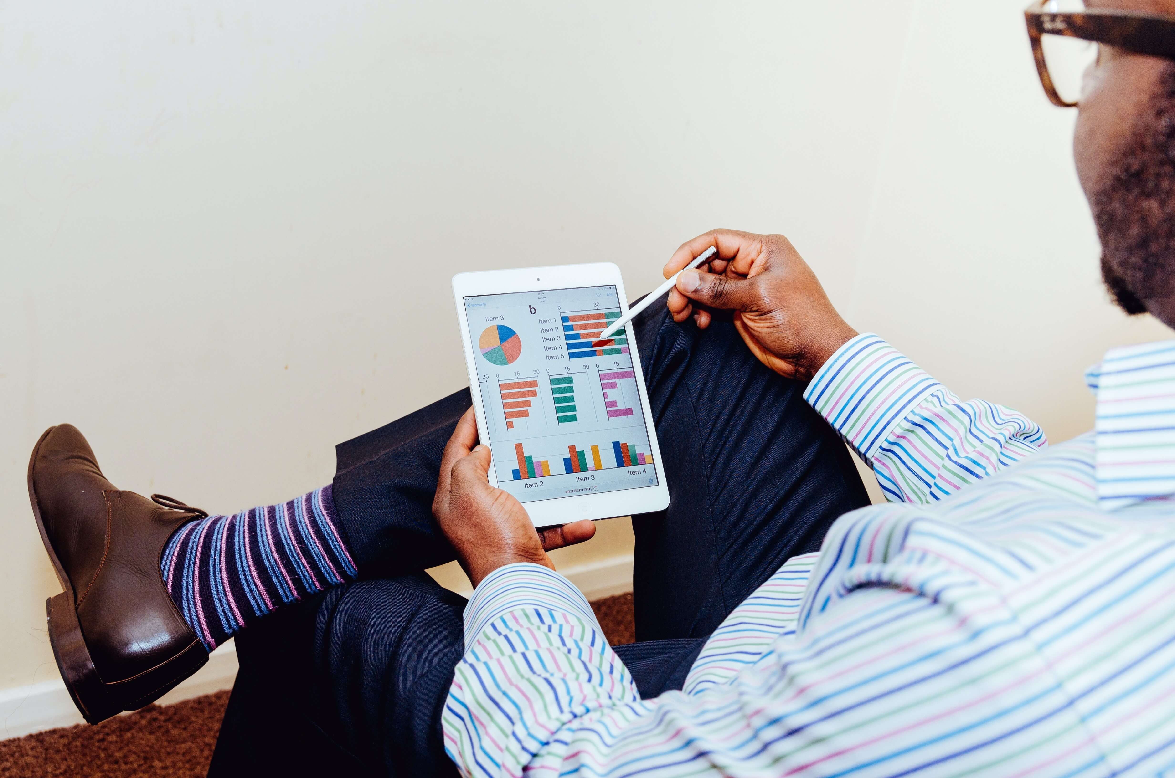 Customer data platform ( CDP ) represented through a man looking at a graphical representation on tablet screen
