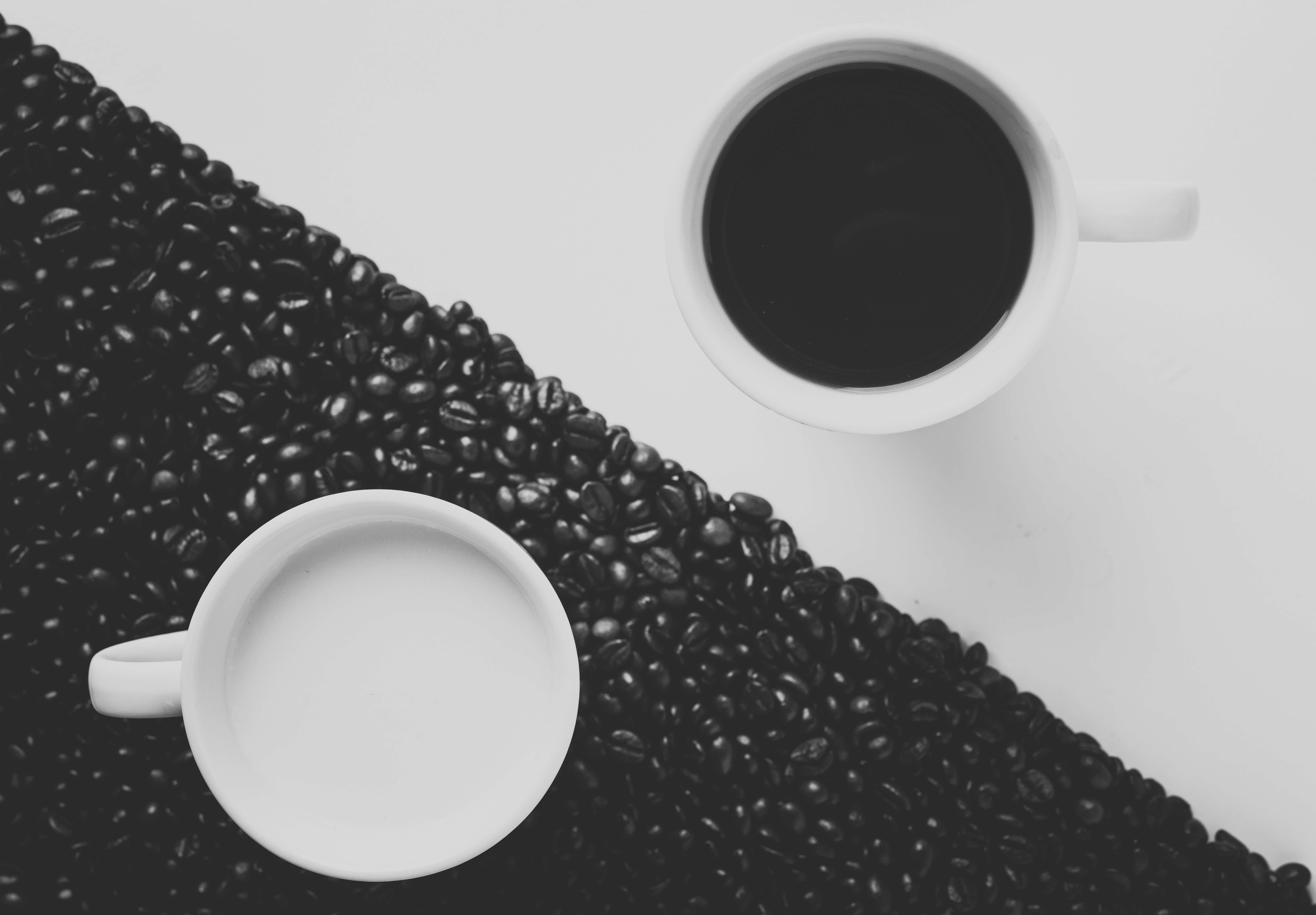 Two coffee mugs placed diagonally opposite to each other and coffee beans scattered around one of the mugs