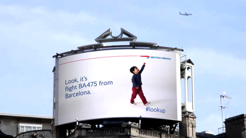 A big screen shows a child pointing his fingers upwards while a plane flies in the sky