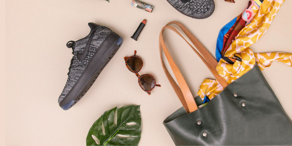 decorational image with a leaf, a pair of shoes, bag, sunglasses and lipstick