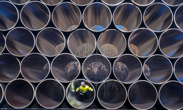 Front view of lots of hollow cylindrical pipes stacked on top of each other with a man sitting inside one of the pipes