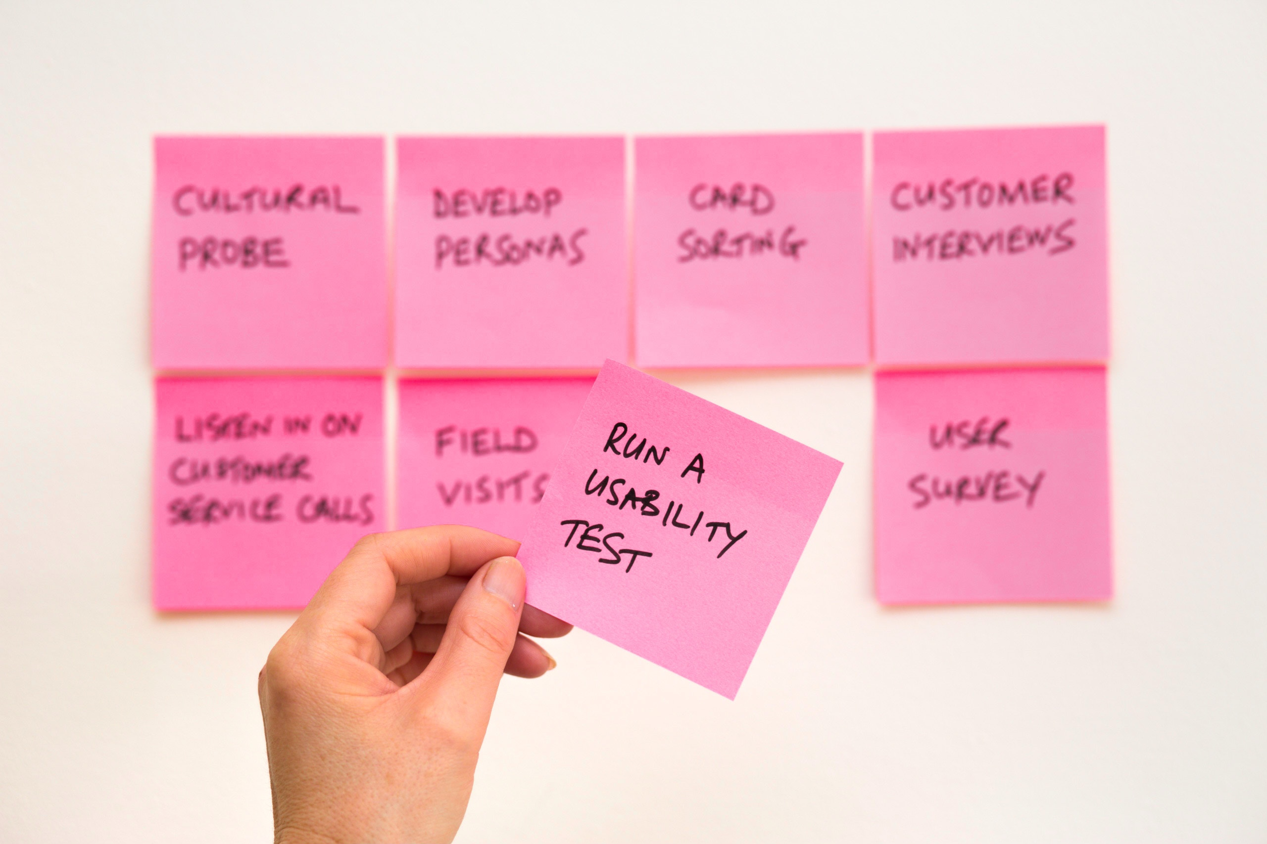 """Sticky notes on a wall with one hand sticky note in focus reading """"Run a usability test"""""""