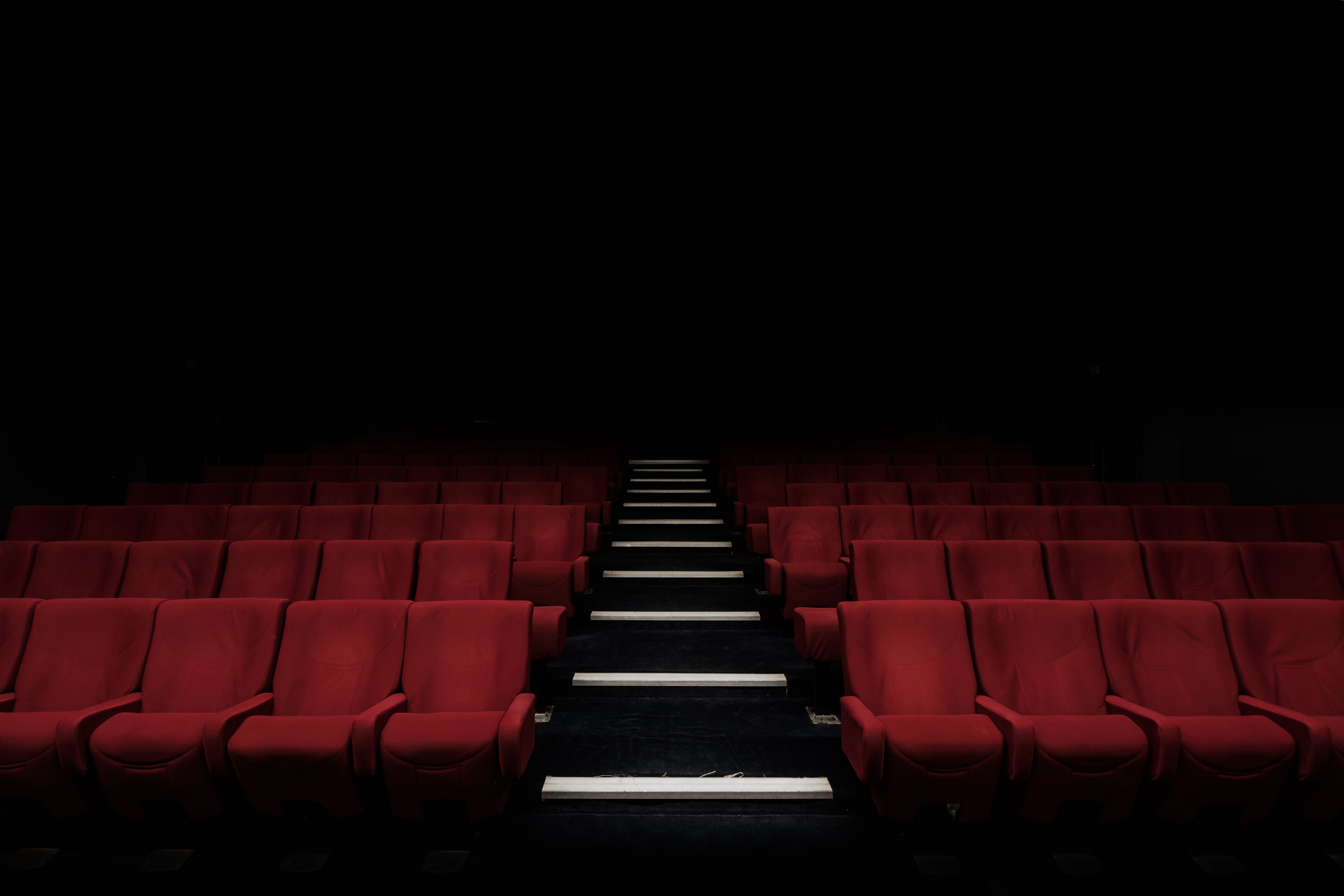 Interior of cinema hall with red chairs