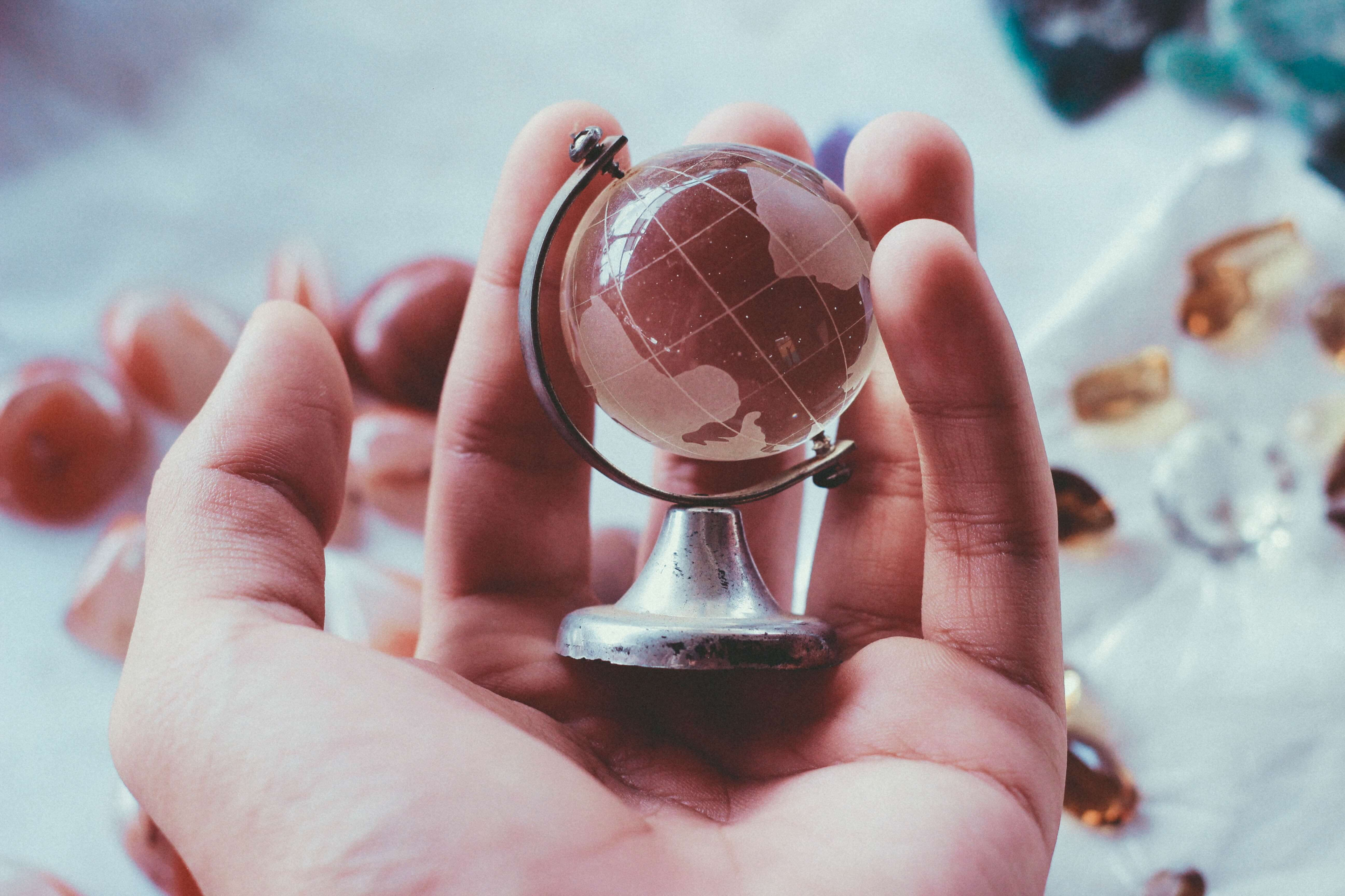 person holding grey metal framed desk globe paper weight