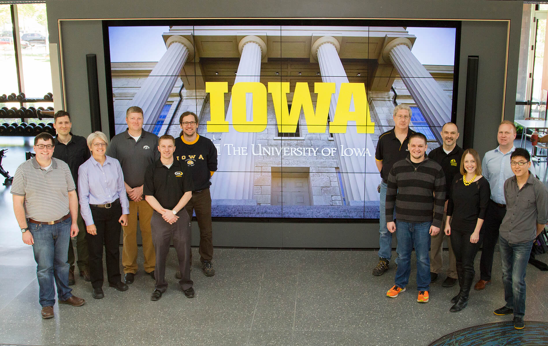 People standing at the sides of the screen showing the pillars and the word IOWA