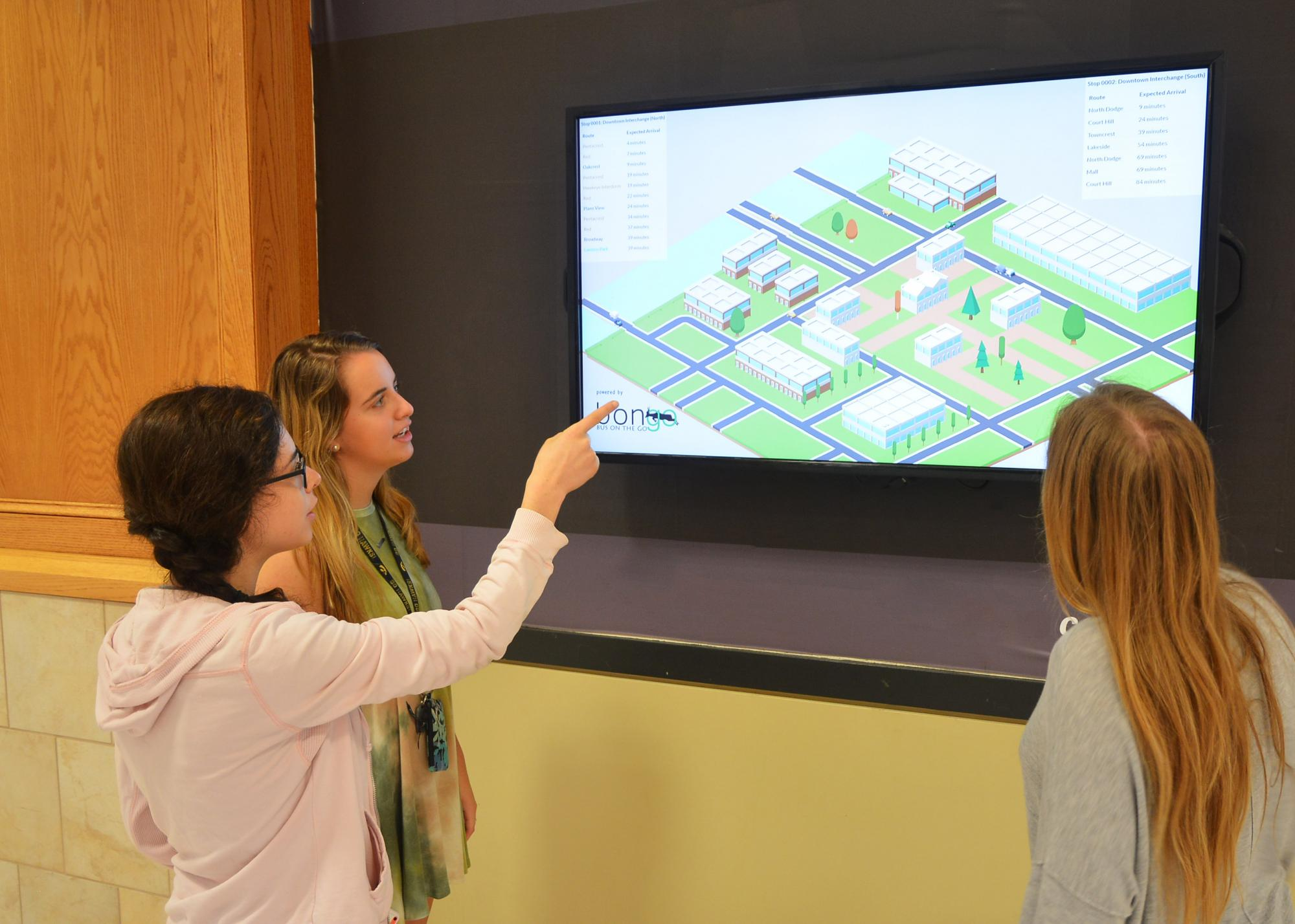 Three girls looking at a screen showing building architecture