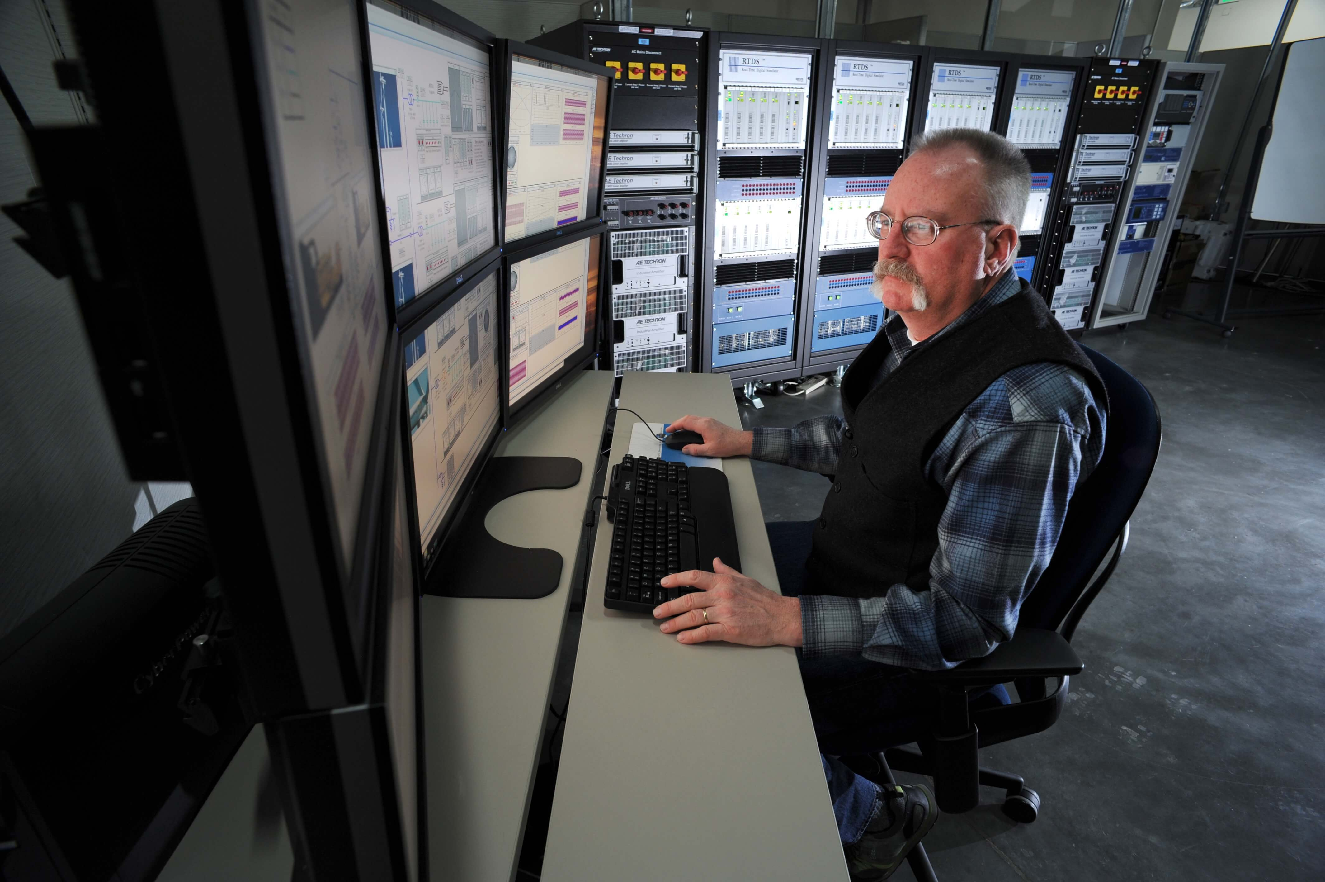 a man sitting in front of multiple screens