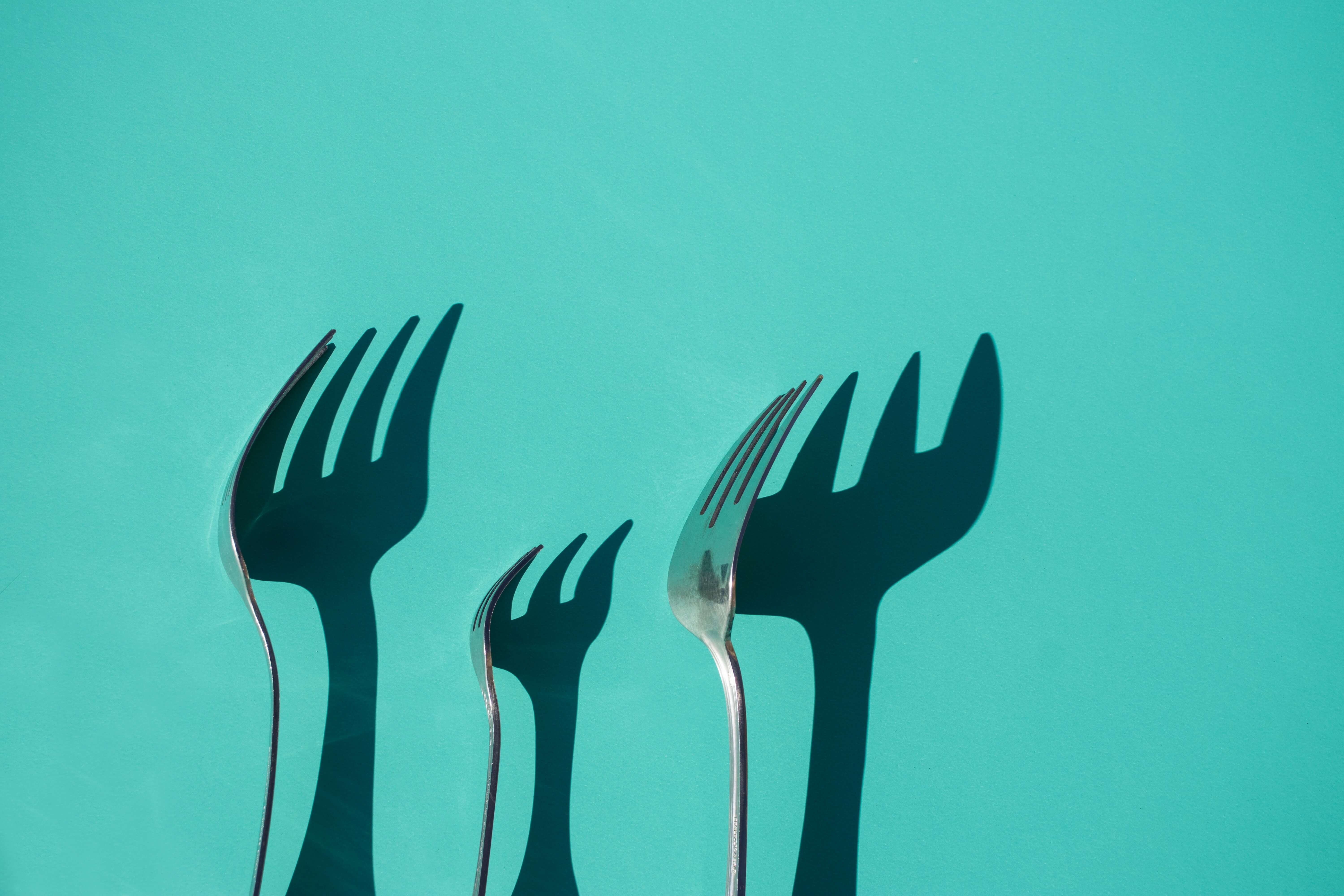 Three forks and their shadows falling on a green background