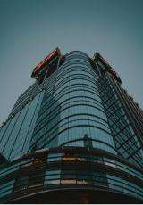 Picture of a large glass building twhich is clicked from the bottom