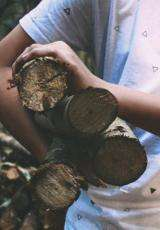 person carrying wood log