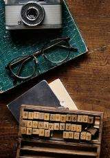 Image of a green notebook on which a camera and glasses are placed with a word constructor games on a wooden background.