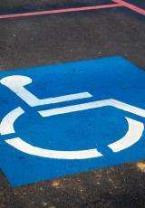 a wheelchair symbol drawn on road in blue and white colours