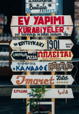beige, red, and brown signages in different languages on beige stand at daytime