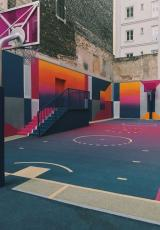 illustration image showing a basketball court with walls painted in multiple colours having net and stairs enclosed by buildings
