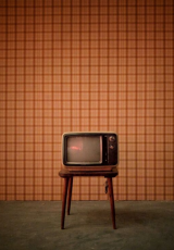 illustration image showing an old television placed on a wooden stool placed on a cemented floor and oraange checkerd wall