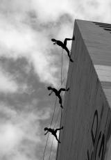 Three people can be seen climbing a wall on a single rope.