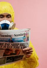 A man in a safety suit and mask is seen reading a newspaper.